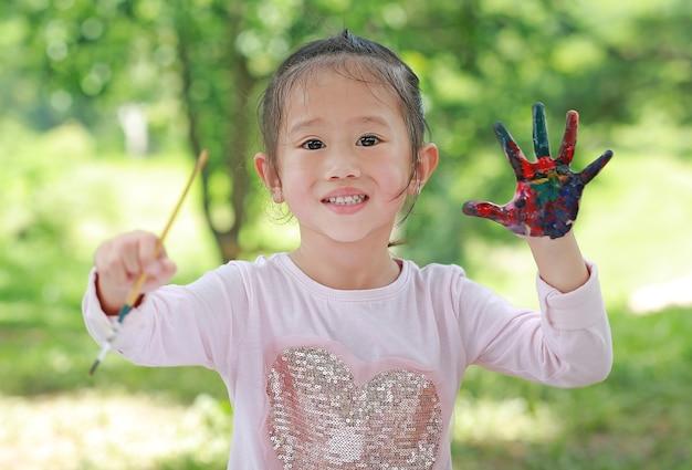 Mignonne petite fille avec des mains peintes dans le parc, le concept de l'éducation de l'éducation.