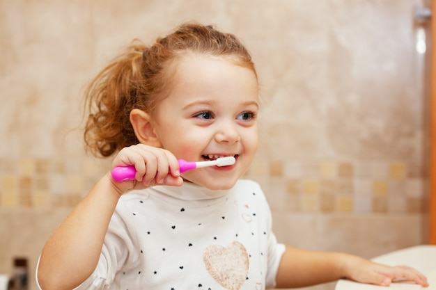 Mignonne petite fille, nettoyage des dents avec une brosse.
