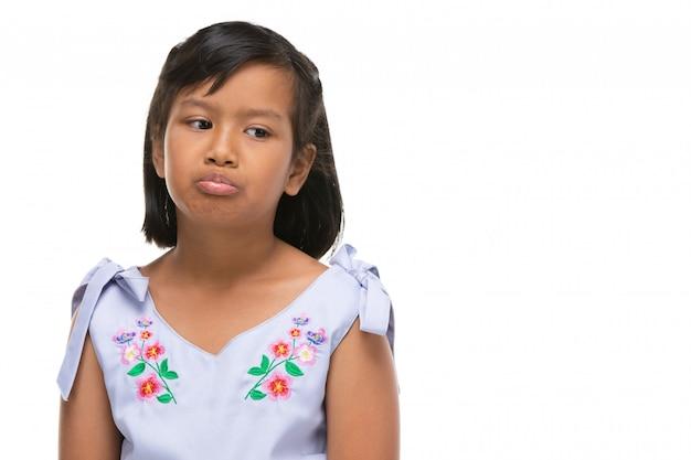 Mignonne petite fille noire asiatique faisant une émotion drôle sur le visage.
