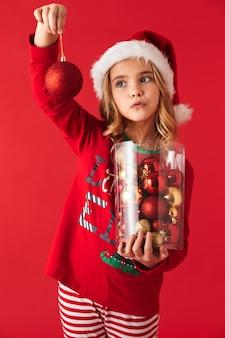Mignonne petite fille portant le costume de noël debout isolé, tenant ensemble de jouets d'arbre de noël