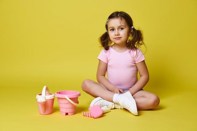 Mignonne petite fille portant des vêtements d'été, assis près d'un ensemble de jouets de plage, regardant la caméra tout en posant sur un mur jaune.