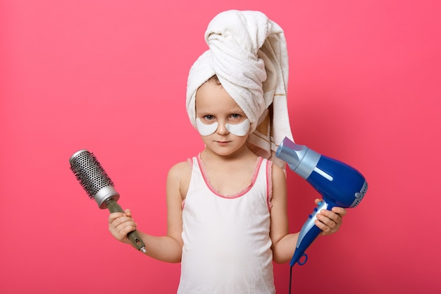 Mignonne petite fille posant avec une sécheuse à brosse ronde et un sèche-cheveux dans les mains