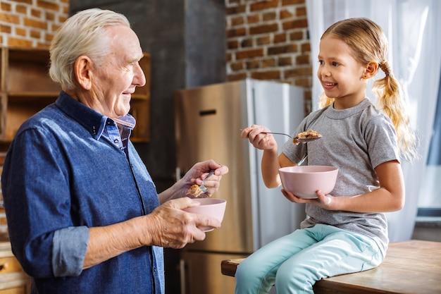Mignonne petite fille positive souriant tout en mangeant le petit déjeuner avec son grand-père