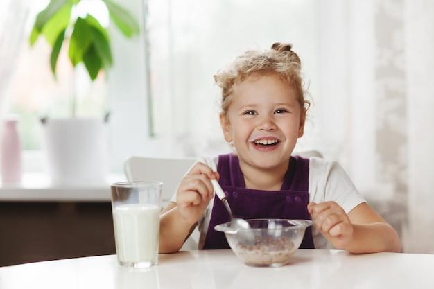 Mignonne petite fille prenant son petit déjeuner