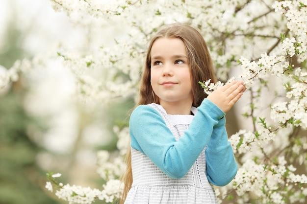 Mignonne petite fille qui marche dans le parc du printemps