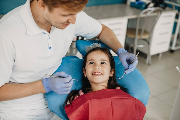 Mignonne petite fille à la recherche de sourire à son jeune stomatologue pédiatrique avant de faire un examen des dents.