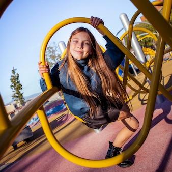 Mignonne petite fille s'amusant sur l'aire de jeux en plein air
