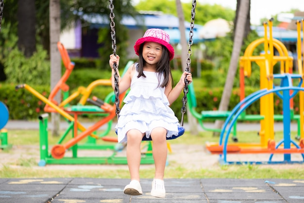 Mignonne petite fille s'amusant avec balançoire dans le parc. aire de jeux pour enfants.