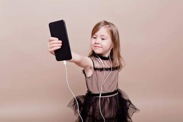 Mignonne petite fille s'amuse et prend selfie. petite fille surprise à la recherche de téléphone et sourit sur un mur isolé, véritable émotion, bonne humeur, élégante petite fille