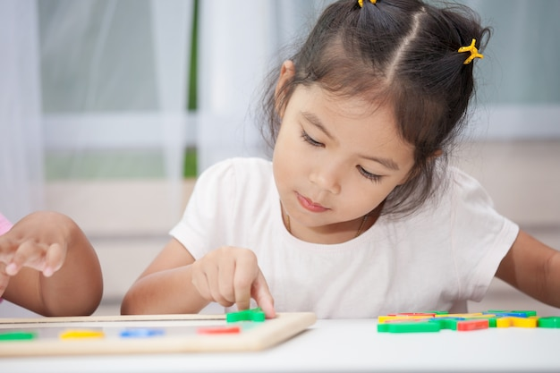 Mignonne petite fille s'amuser à jouer et apprendre les alphabets magnétiques à bord dans la chambre