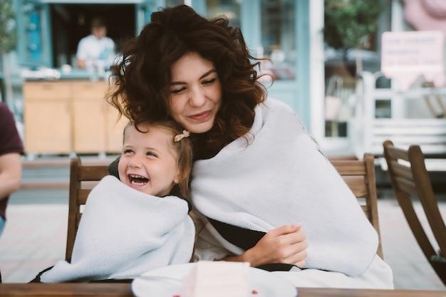 Mignonne petite fille et sa belle jeune maman s'embrassent, à l'extérieur