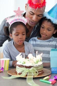 Mignonne petite fille et sa famille célébrant son anniversaire