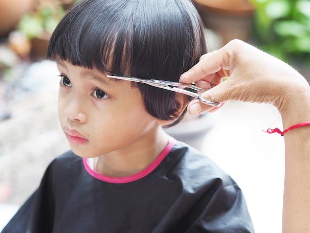 Mignonne petite fille se coupe les cheveux