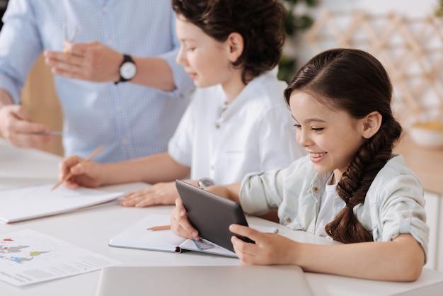 Mignonne petite fille se distraire de ses devoirs à domicile en jouant sur sa tablette pendant que son père et son fils font des sommes derrière