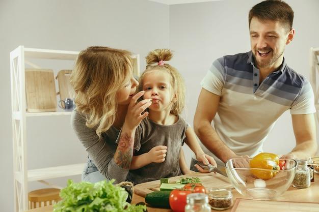 Mignonne petite fille et ses beaux parents coupent des légumes et sourient tout en faisant une salade dans la cuisine à la maison. concept de mode de vie familial
