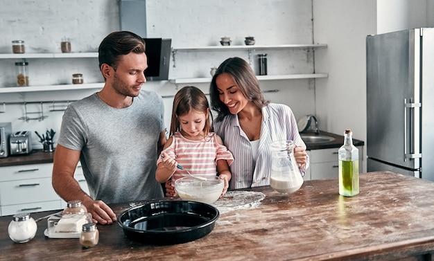 Mignonne petite fille et ses beaux parents pétrissent la farine pour la cuisson et sourient en cuisinant dans la cuisine.