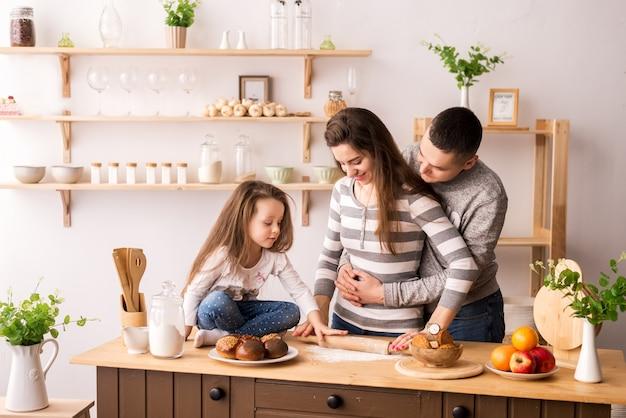 Mignonne petite fille et ses beaux parents préparent la nourriture et sourient en cuisinant dans la cuisine à la maison. pétrir la pâte sur des crêpes et des petits pains