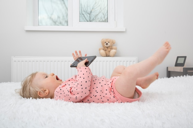 Mignonne petite fille avec un smartphone dans la chambre des parents.