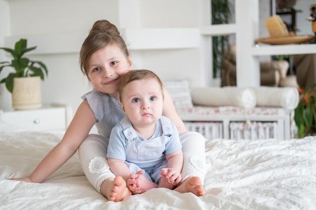 Mignonne petite fille sœur aînée avec son petit frère à la maison assis sur le lit.