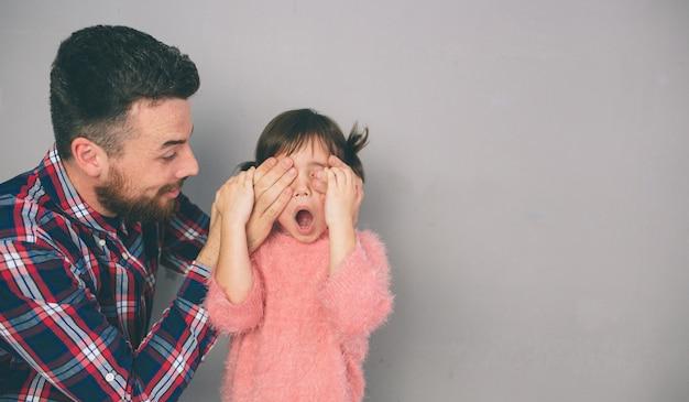 Mignonne petite fille et son beau jeune papa jouent ensemble dans la chambre d'enfant. papa et l'enfant passent du temps ensemble assis sur le sol dans la chambre.
