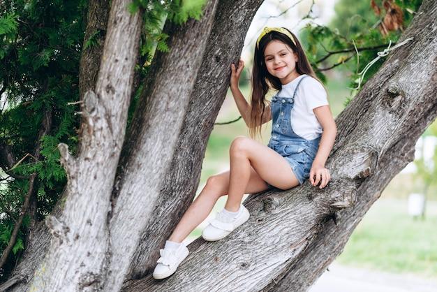 Mignonne petite fille souriante assise sur l'arbre dans le parc et regardant la caméra.