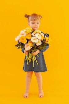 Mignonne petite fille tenant des fleurs