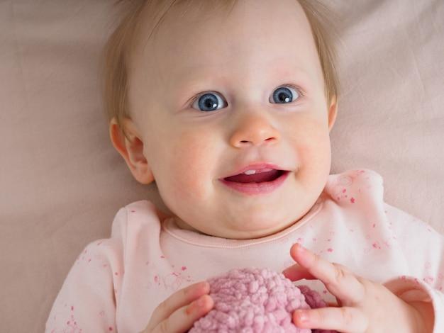 Mignonne petite fille tendre, 10 mois, une dent, lève les yeux avec surprise, gros plan. portrait d'une jeune fille dans les tons roses. concept de produits pour bébé. les vraies émotions des enfants.