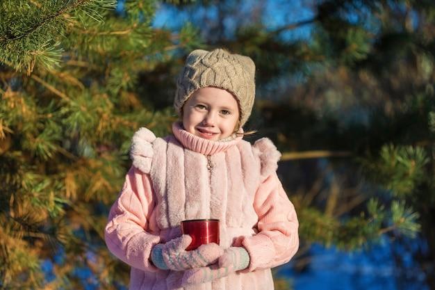 Mignonne petite fille tient une tasse de thé chaud dans la forêt d'hiver. enfance heureuse. enfants à l'extérieur concept de vacances d'hiver amusant