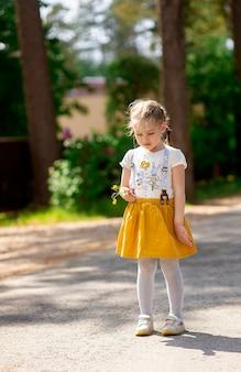 Mignonne petite fille avec une triste émotion en colère sur son visage se tient seule sur une route de campagne