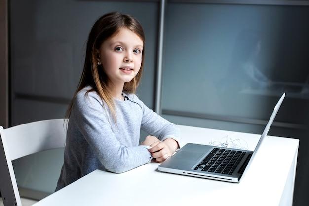 Mignonne petite fille utilisant un ordinateur portable à la maison pour l'éducation en ligne et l'apprentissage à distance pour les enfants