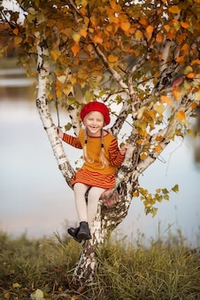 Mignonne petite fille en vêtements tricotés dans le parc d'automne