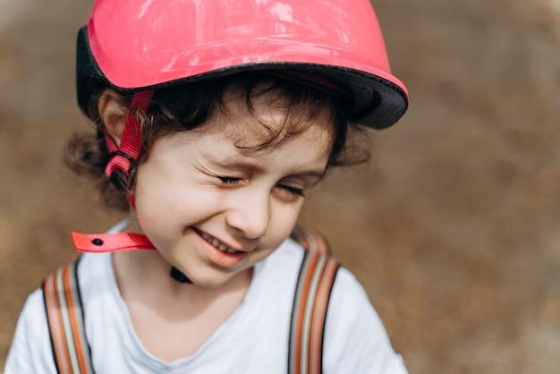Mignonne, souriante, enjouée, petite fille cligne de l'œil. la fille dans un casque de protection.
