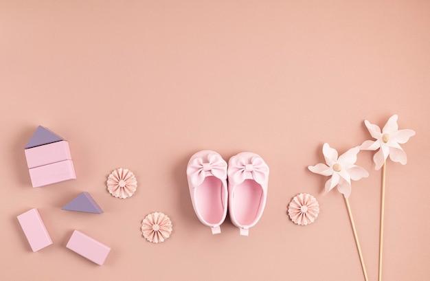 Mignonnes chaussures de bébé nouveau-né avec décoration festive sur mur rose.