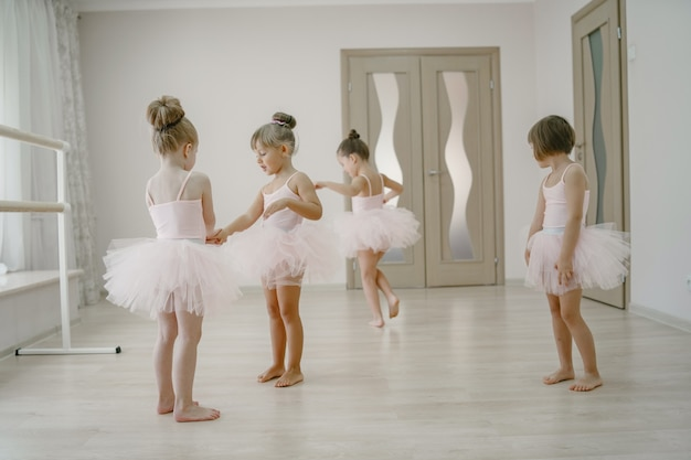 Mignonnes petites ballerines en costume de ballet rose. les enfants dans une pointe danse dans la salle