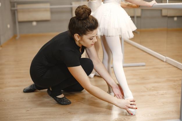 Mignonnes petites ballerines en costume de ballet rose. les enfants en pointes dansent dans la salle. enfant en cours de danse avec professeur.