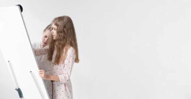 Mignonnes petites filles dessinant sur tableau blanc avec espace copie