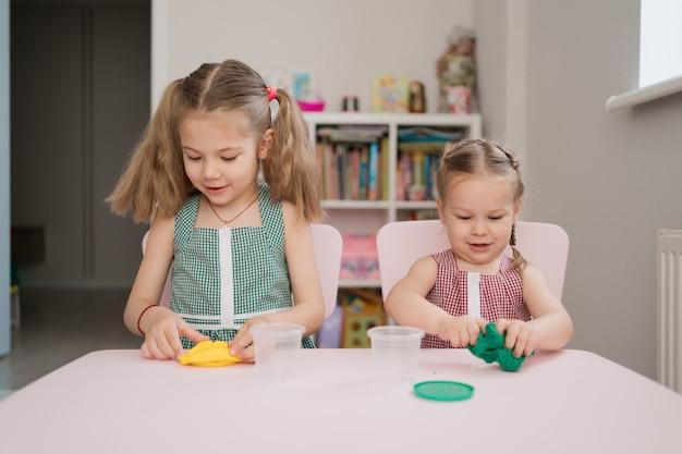 Mignonnes petites filles moulant de pâte à modeler sur table rose