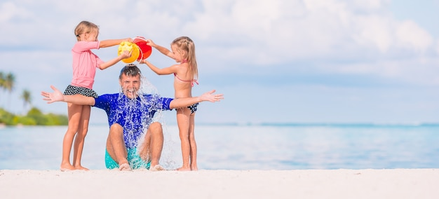Mignonnes petites filles s'amusant avec papa sur la plage blanche