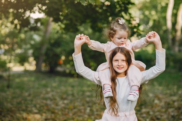 Mignonnes petites soeurs jouant dans un parc de printemps
