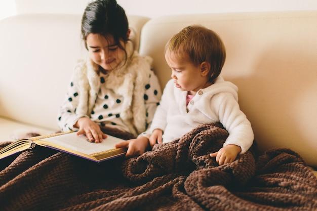 Mignonnes petites sœurs lisant un livre dans le lit