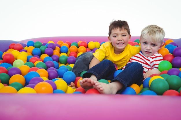 Mignons garçons souriants dans une piscine à balles éponge en regardant la caméra