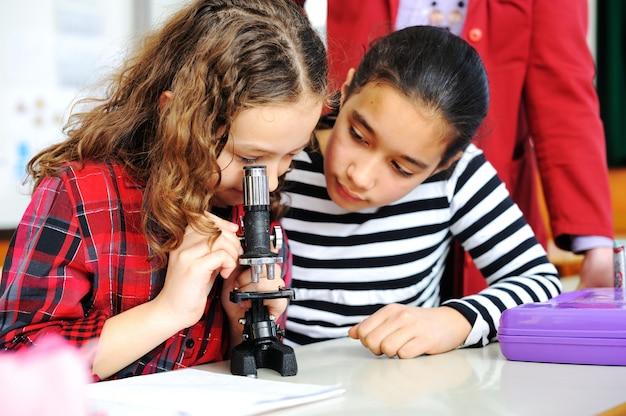 Mignons jolis écoliers à clasroom ayant des activités éducatives