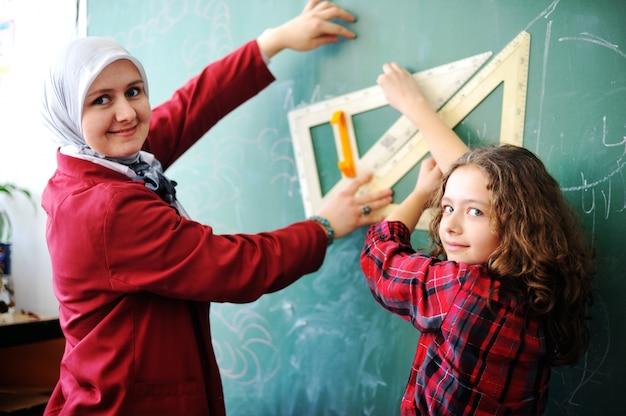 Mignons jolis écoliers en classe ayant des activités éducatives