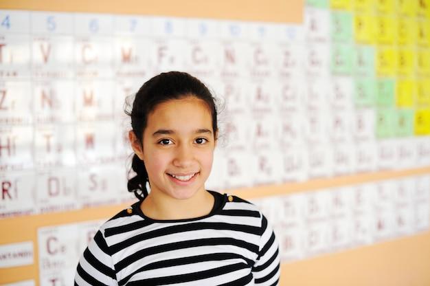 Mignons jolis écoliers en classe avec tableau périodique des éléments
