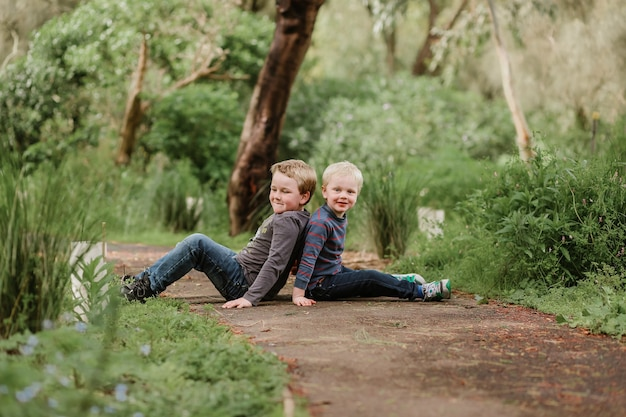 Mignons petits enfants blonds assis par terre dans un parc et jouant