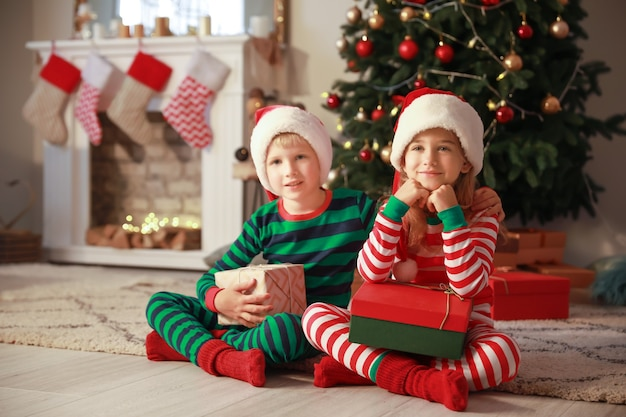 Mignons petits enfants avec des cadeaux de noël à la maison