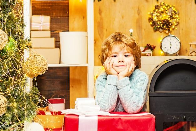 Mignons petits enfants célébrant noël. portrait de santa kid avec un énorme cadeau rouge regardant la caméra