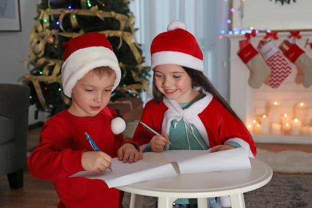 Mignons petits enfants écrivant une lettre au père noël à table