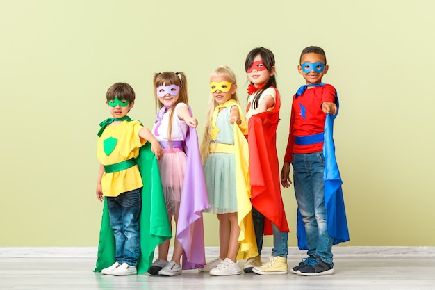 Mignons petits enfants habillés en super-héros près du mur de couleur