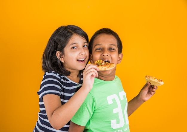 Mignons petits enfants indiens ou asiatiques mangeant de délicieux hamburgers, sandwichs ou pizzas dans une assiette ou une boîte. debout isolé sur fond bleu ou jaune.